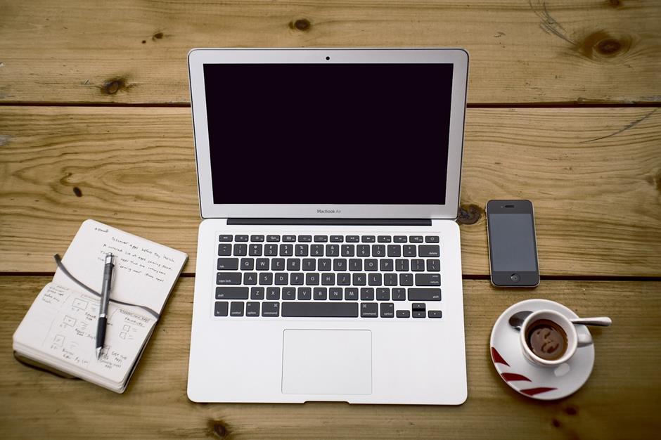 Arbeitsplatz mit Notizbuch, Macbook, Iphone und Kaffee