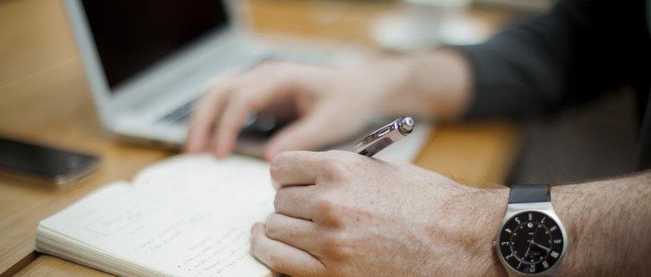 Arbeitsplatz im Notizbuch schreiben